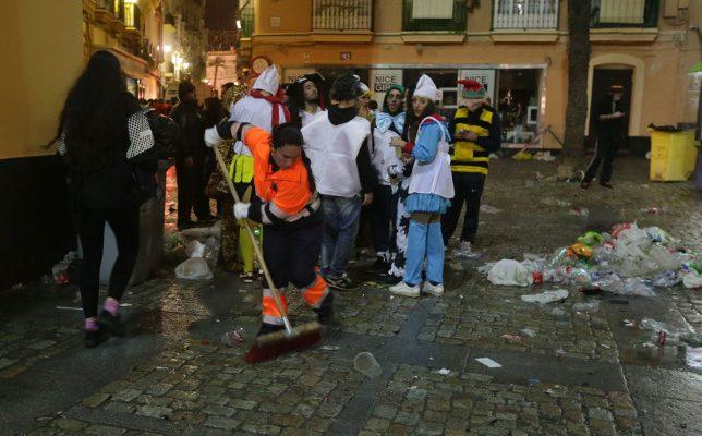 Una limpiadora recoge la suciedad de la calle en el Carnaval de Cádiz. Desalojo Viña Polémica